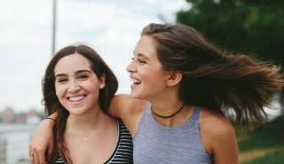 Two models with soft hair, hugging and smiling.