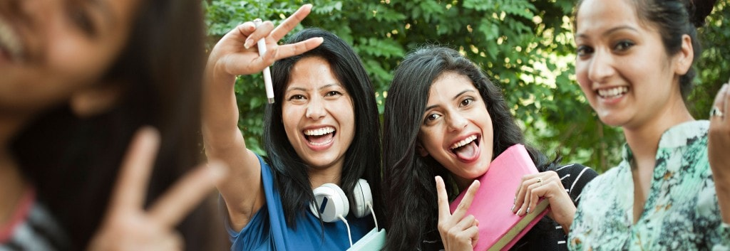 Two women laughing and making two fingered peace gestures towards the camera. One wears large headphones and holds a school notebook.