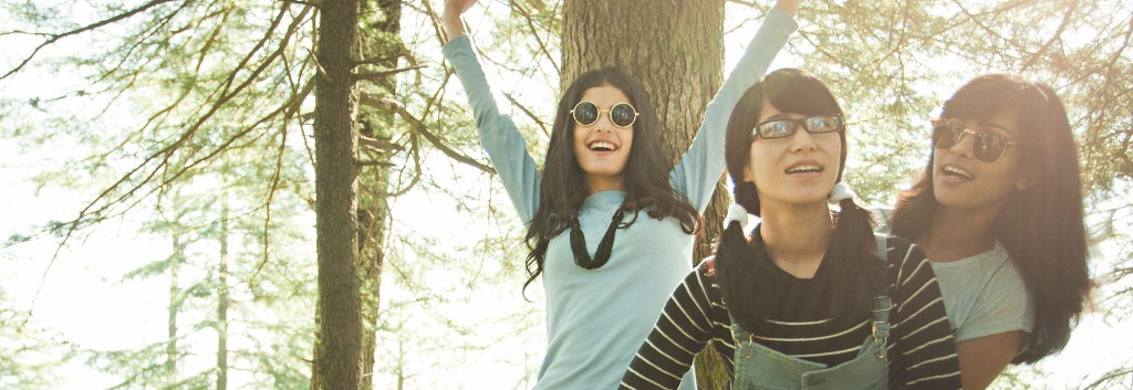 Three young women with long, thick black hair standing around looking cheerful in a sunny woodland.