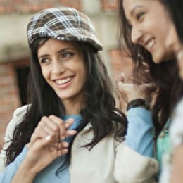 Close up of a smiling woman wearing a stylish checkered hat.