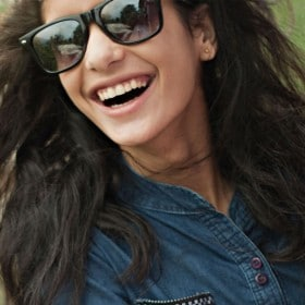 Two girlfriends wearing sunglasses and laughing together.
