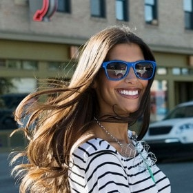 A stylish woman with bright blue sunglasses crossing the street and smiling as the wind blows her long, sleek brown hair.